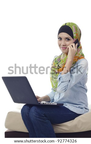 Beautiful muslim woman with computer and make a phone call isolated on white background
