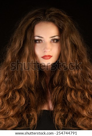 Beautiful mysterious young brunette woman with amazing curly hair. Hair products model. Fantasy woman portrait. Book cover.