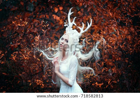 Beautiful mystery gothic woman in long white dress with deer horns in autumn forest. Dark fantasy creature elf in magic wood #718582813