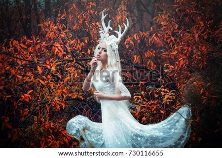 Stock Photo Beautiful mystery gothic woman in long white dress with deer horns in autumn forest. Dark fantasy creature elf in magic wood. Helloween dress style