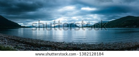 Beautiful mystic landscape lake scenery in Scotland with cloudy sky and sunbeams #1382128184