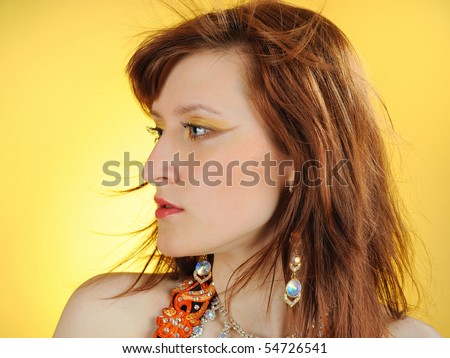 Beautiful mystic woman with golden make-up in belly dance costume. yellow background