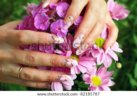 Beautiful nail design. Woman hands with chrysanthemums flowers.