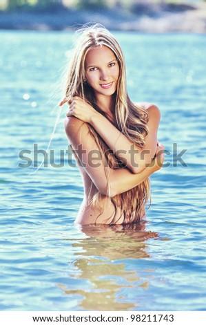 Beautiful naked woman in lake water