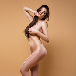 Beautiful Naked Woman Posing Isolated On The Beige Background