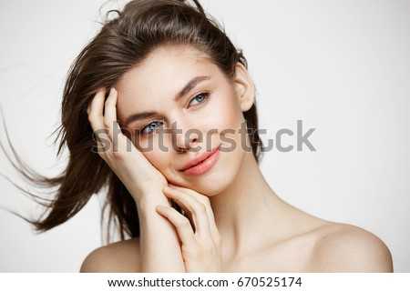 Beautiful naked young girl with perfect clean skin smiling touching hair over white wall. Facial treatment. #670525174
