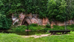 Beautiful natural formation. A naturally formed cave in the sandstone rock - Angel's Cave. A river flows along the cave. Devonian period. Skaņākalns Nature Park. Mazsalaca. Latvia. Tourist objects