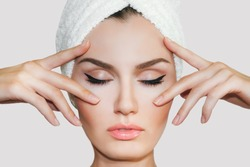 Beautiful natural girl woman after cosmetic procedures ,face-lift , facial massage , visit a beautician , massage lines. Beautiful female with a towel on his head.  Spa treatments