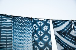 Beautiful natural indigo tie dye fabric hanging outdoor under the blue sky. Indigo dyed fabric in Chiang Mai, Thailand.