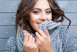 Beautiful natural looking young smiling brunette woman, wearing knitted scarf, covered with snow flakes. Snowing winter beauty concept.