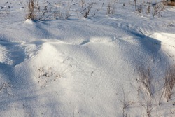 beautiful natural phenomena of the winter season, covered soil and grass with a thick layer of snow after a cyclone with storms and snowfalls, cold frosty winter weather and snow drifts