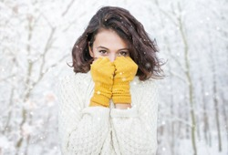 Beautiful natural young smiling brunette woman wearing knitted sweater and glove in the woods. Snowing snow winter concept.