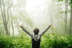 Beautiful nature in the fog and man. Girl with hands up with a backpack.
