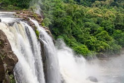 Beautiful nature view during Monsoon time with full filled water fall and green forest from the famous tourist place in Kerala, India called Athirappalli and Vaazhachaal