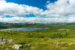 Beautiful nature view of the vastness of the Swedish highlands, with snow-covered mountain tops, lakes, and low growing green trees in summer sunlight