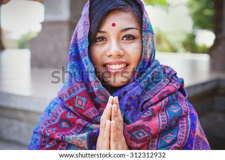 beautiful nepalese woman saying and performing namaste gesture