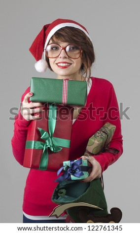 Beautiful nerdy girl  with santa's hat holding a presents