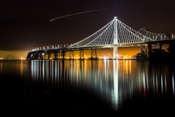 Beautiful new East Span Bay Bridge at night illuminated reflecting Oakland port color lights cityscape. The iconic and majestic bridge after dark long exposure in San Francisco greets traveler.