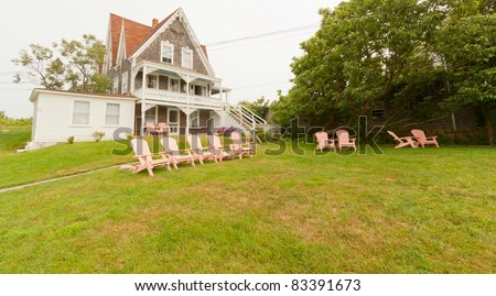 Beautiful New England vacation summer home with a row of pink lawn chairs.