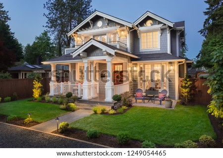 Beautiful New Home Exterior at Night: Home with Green Grass and Covered Porch, including Stately Gables and Columns.  #1249054465