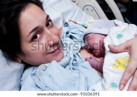 Beautiful new mother happy holding her infant baby after giving birth in hospital.