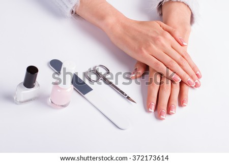 Beautiful new women\'s french manicure and tools for manicure on a white background.