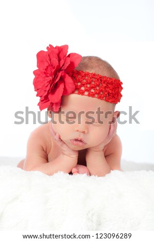 Beautiful newborn baby girl sleeping with head on hands on a fluffy white blanket and wearing a pretty red flower head band