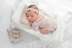 Beautiful newborn baby girl wearing lace costume ana wreath lying on her tummy on stylized white bed with pillow during studio photoshoot. Cute portrait of infant child in white room from above