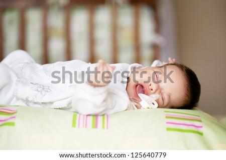 Beautiful newborn baby lying in his bed