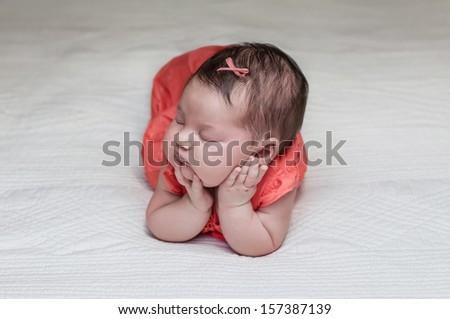 Beautiful newborn baby posing sleeping on her elbows and hands