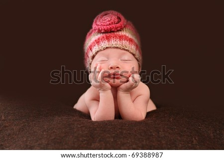 Beautiful newborn baby resting her hands on her face