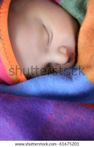 Beautiful newborn boy wrapped in a colorful blanket