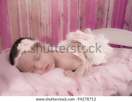 Beautiful newborn girl asleep in her bed with white ruffled bloomers with a pink bow and beautiful headband of yarn and ribbon and a fabric pink flower,