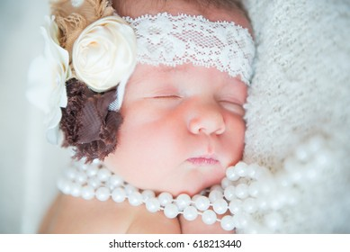 Stock photo of beautiful newborn sleeping baby with cute props