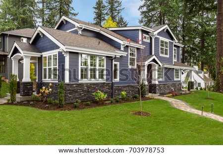 Beautiful, Newly Built Luxury Home Exterior with Green Lawn and Forest Backdrop, as Seen From Angle