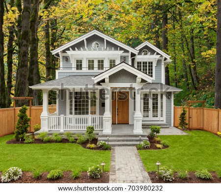 Beautiful, Newly Built Luxury Home Exterior with Lush Forest in Background #703980232