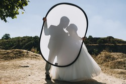 Beautiful newlyweds hold a photo reflector with their hands on the background of nature. Wedding silhouette kiss of the bride and groom in front of the sun.