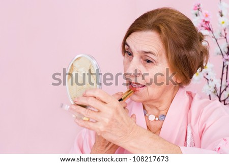 Beautiful nice old woman sitting at a table on a pink background