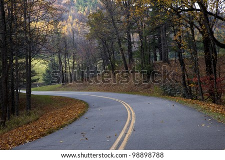 Beautiful, nicely paved winding road lined with colorful autumn leaves
