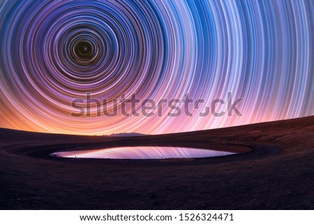 Photo of  Beautiful night landscape, old volcano, crater lake. The colorful star trails on the sky. Night timelapse photography.
