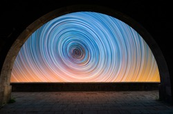 Beautiful night landscape. View from the arch to the colorful star trails on the sky. Night time lapse photography.