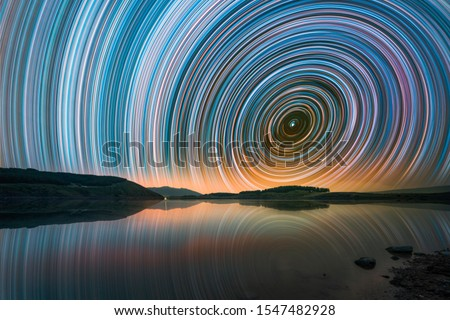 Photo of  Beautiful night landscape with small lake and mountains. The colorful star trails on the sky. Night time lapse photography.