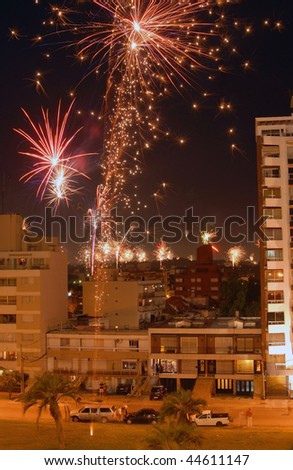 Beautiful night scene celebration of new year with fireworks over the buildings. Montevideo, Uruguay