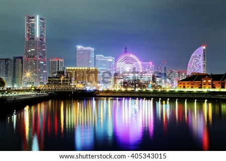 Beautiful night scenery of Yokohama Minatomirai Bay area with high rise buildings in the background, a giant Ferris wheel in Cosmo World Amusement Park & colorful reflections of city lights on water stock photo