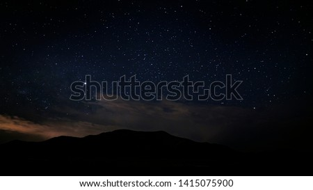 Beautiful night sky in the Utah desert on a summer night with a mountain in the background.