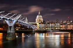 Beautiful night view of the illuminated dome of St Paul's Cathedral in the City of London, London, UK, with the River Thames and the modern Millennium Bridge