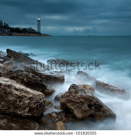Beautiful nightly seascape with lighthouse on the island