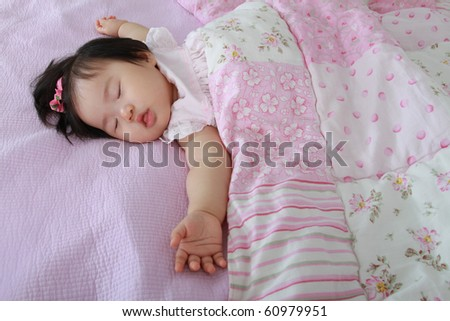 Beautiful Nine Month Old Asian Baby Infant Girl Sleeping with Arms Akimbo on Bed