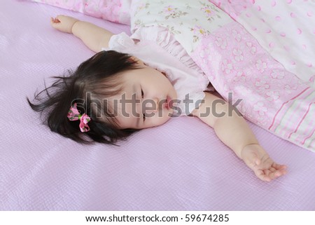 Beautiful Nine Month Old Asian Baby Infant Girl with pink bow in hair under blanket just waking up