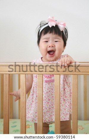 Beautiful Nine Month Old Baby Asian Infant Girl in pink dress with pink ribbon in wooden crib screaming